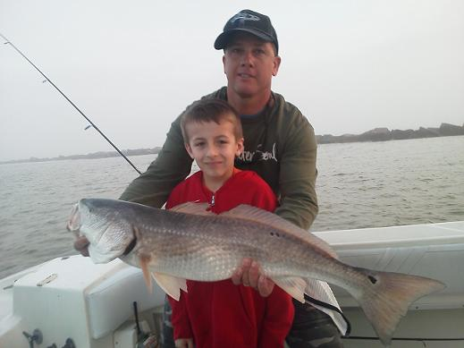 Capt. Greg with child showing off his fishing charter catch